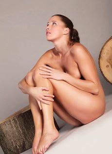 Красивая модель раздевается на деревянном полене - фото #