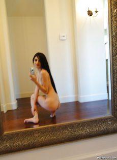 Перед зеркалом очаровательная брюнетка демонстрирует голое тело - фото #