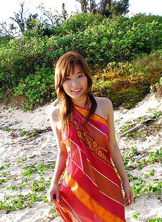 Азиатская девушка оголила свое стройное тельце на берегу моря - фото #
