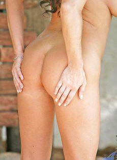 На улице брюнетка в возрасте сексуально раздевается - фото #