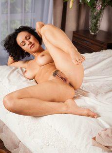 Кудрявая брюнетка обнажилась и разлеглась на просторной кровати - фото #9