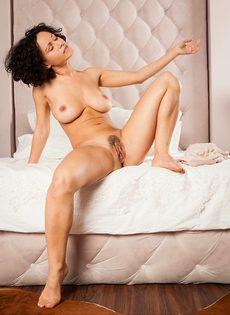 Кудрявая брюнетка обнажилась и разлеглась на просторной кровати - фото #10