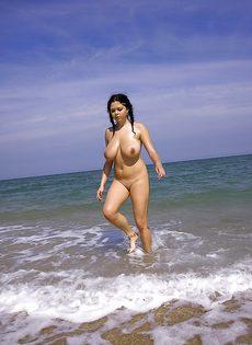 Темноволосая потаскуха хвастается большими дойками на пляже - фото #16