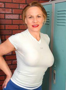 Спортивная женщина с большими сиськами позирует в раздевалке - фото #1