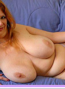 Женщина позирует лежа на диване своими крупными сиськами - фото #