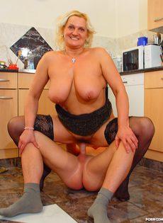 Зрелая дамочка в черных чулках задорно прыгает на молодом члене - фото #
