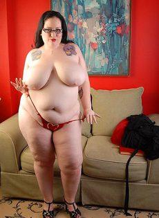 Очень толстая зрелая женщина в очках снимает черное платье - фото #