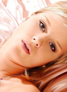 Обнаженная блондиночка с большими грудями ласкает бритую киску на кровати - фото #