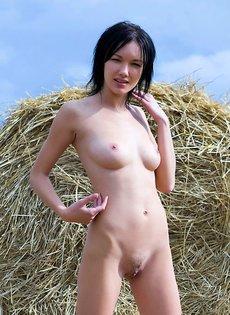 Деревенская сучка позирует обнаженной возле стога с сеном
