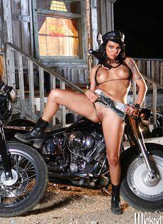 Жаркая брюнетка позирует голой возле мотоцикла