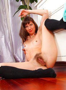 Зрелая бабенка сидит на полу и показывает волосатую дырку