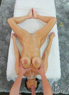 Намасленная брюнетка лежит на массажной кушетке и сосет большой член