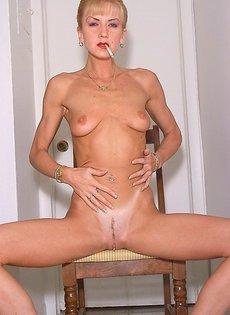 Голая женщина курит и ласкает себя между ног